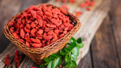 Goji berries in the basket on the rustic table