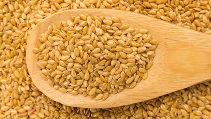 Golden Flax seed. Grains in wooden spoon. Close up.