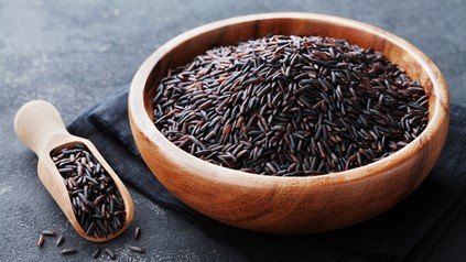 Black rice in wooden bowl on a dark table