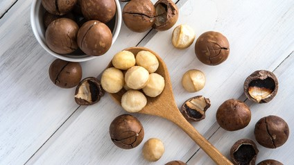 Close up Macadamia nuts on  white wooden background , superfood and healthy food concept , overhead or top view shot with vintage color tone