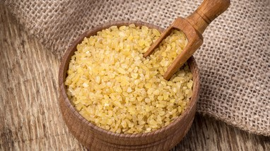 Raw Bulgur (on wooden background)