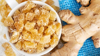 Candied ginger on wooden background
