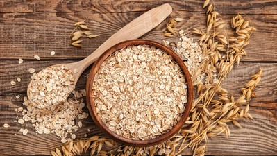 oatmeal in a bowl and spoon old board on top. Spikes of oats