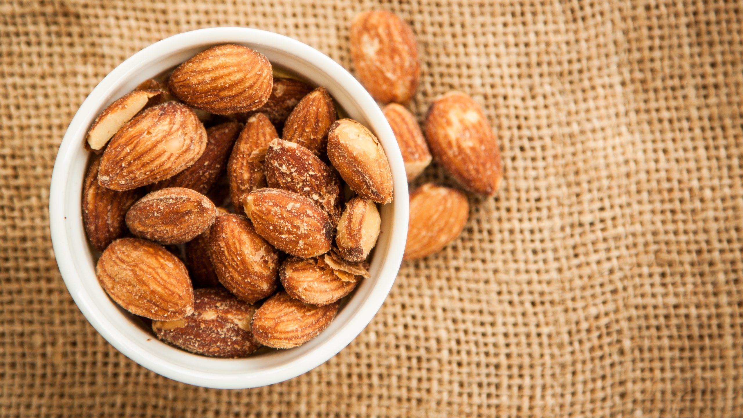 Close up Almonds with salted and Roasted in the white cup put on the sackcloth and wood floor, the great snack